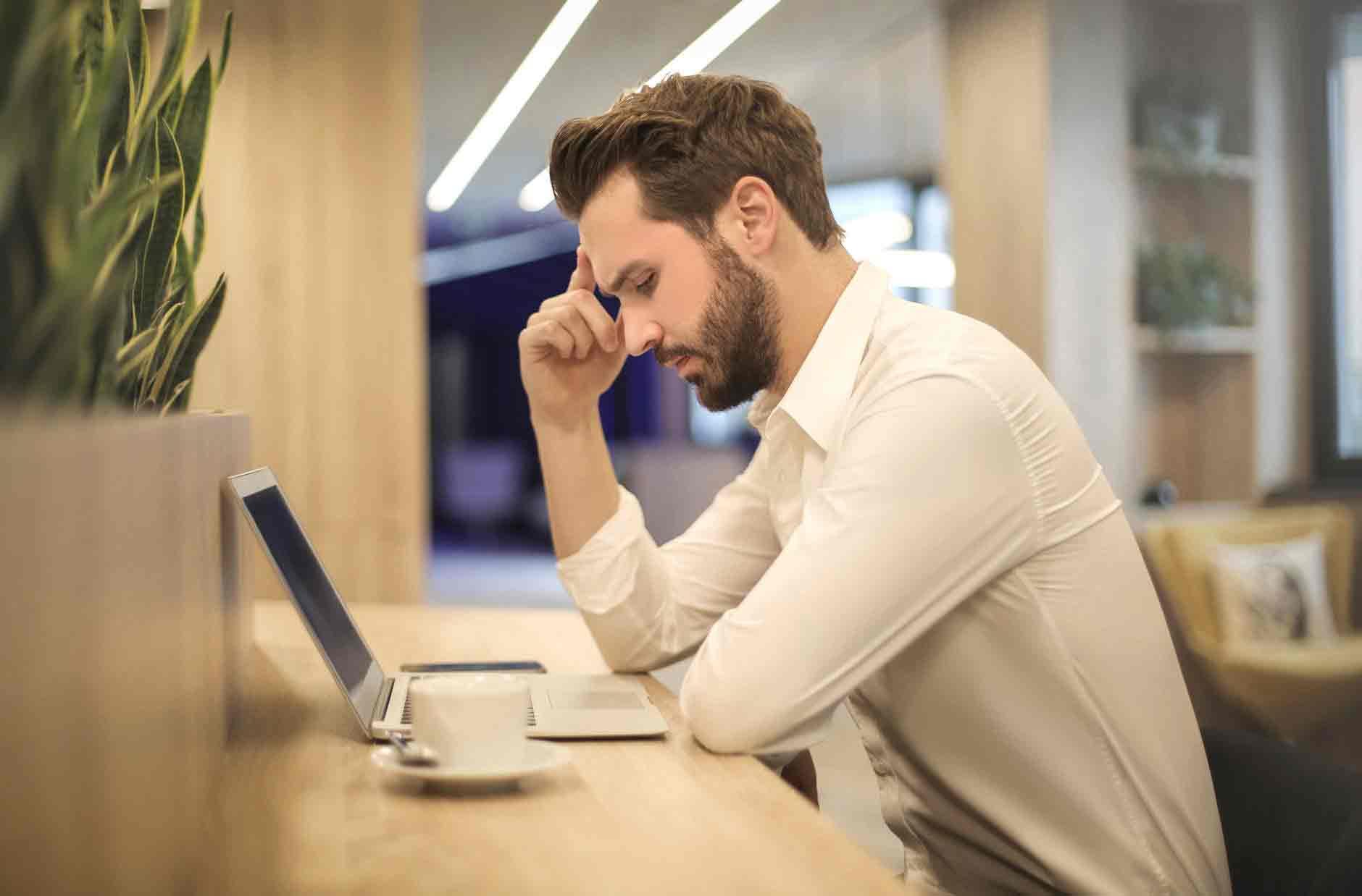 Problema Jurídico. Foto: homem sentado no computador pensando sobre o seu problema e como o solucionar.jpg