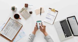 Acúmulo de função. Foto de mulher mexendo no celular em uma mesa de negócios