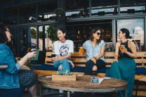Soft Skills o que são. Foto de mulheres sentadas em uma mesa, conversando e rindo.